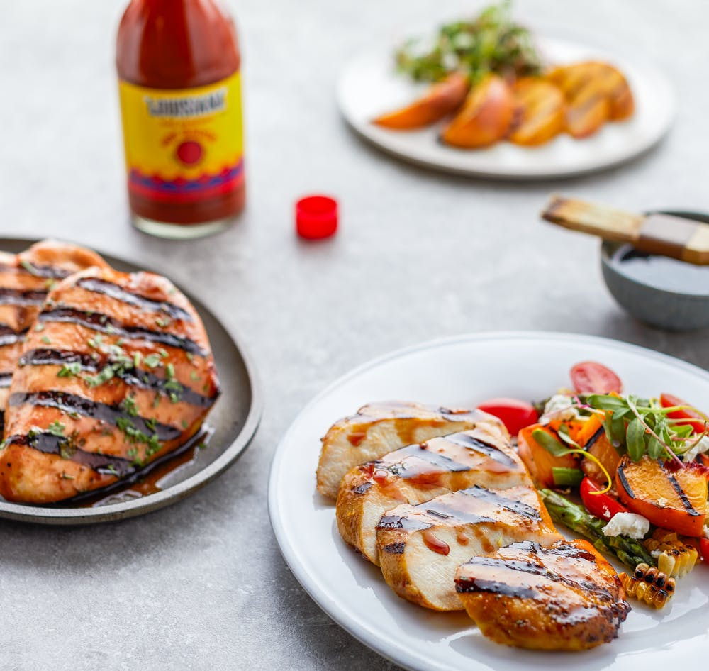 A set table featuring chicken dishes made with Louisiana Hot Sauce.