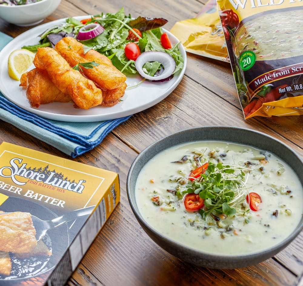 A set table featuring Shore Lunch products and soups and fish dishes made with Shore Lunch products.